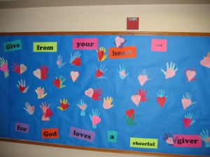 A bulletin board of hearts & hands made by the kids