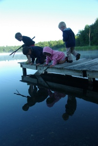 Kids intently focused on the lake, from a dock