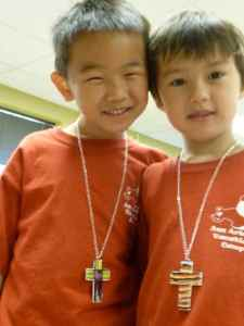Two boys show off their crosses
