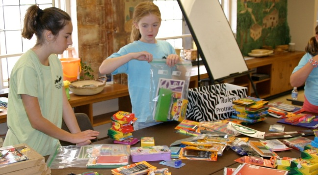 Kids work on creating school kits