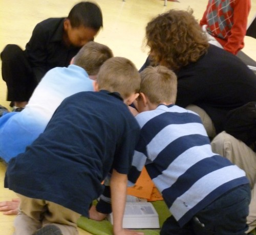 A group of kids works together to determine an answer