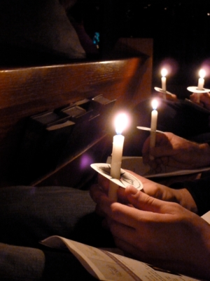 In the pews at a Christmas eve service with candles