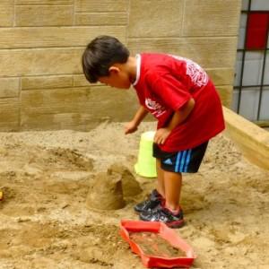 a preschooler builds a sand castle