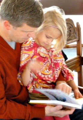 A 3rd grader checks out her new Bible with dad