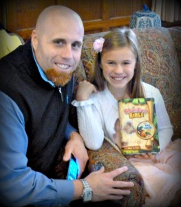 A 3rd grader proudly holds her Bible