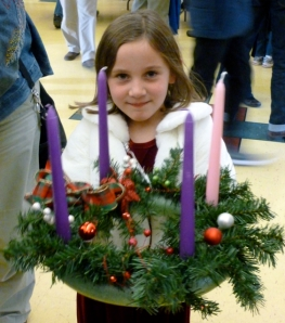 a child holds a newly created Advent wreath