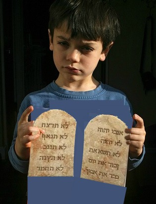 A quizzical-looking boy holds what appears to be ten commandment tablets