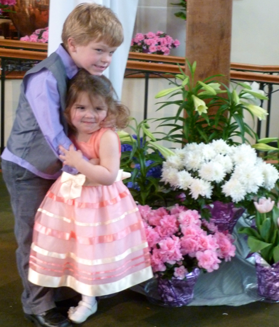 Two kids in Easter finery at the base of the flower-decked cross
